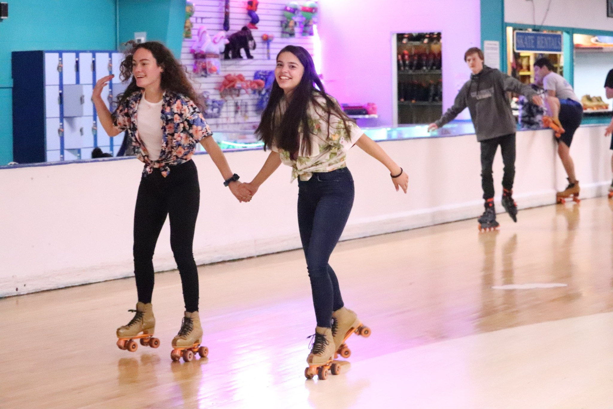 Two girls skating and holding hands