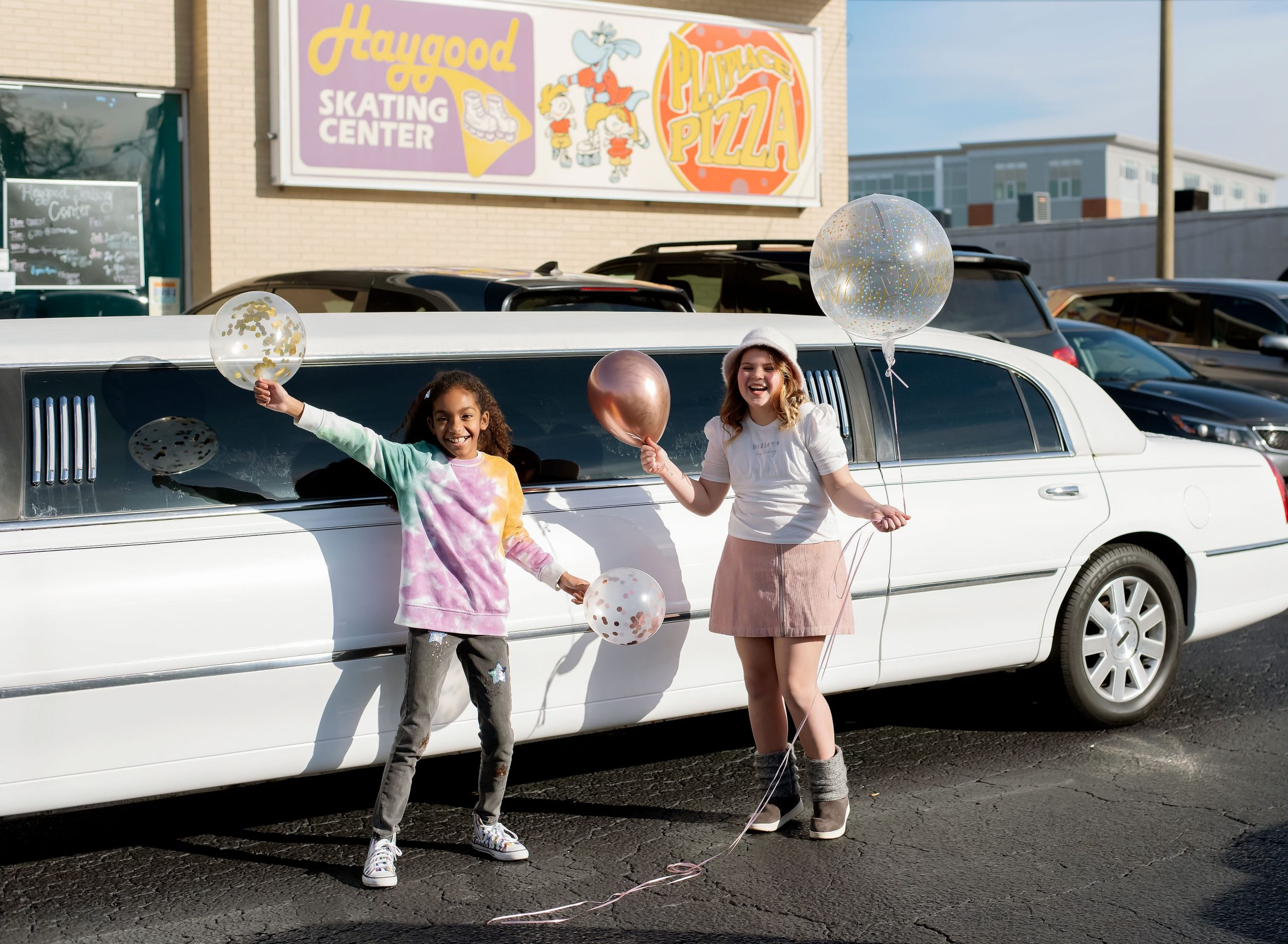 Girls standing outside of limo before party