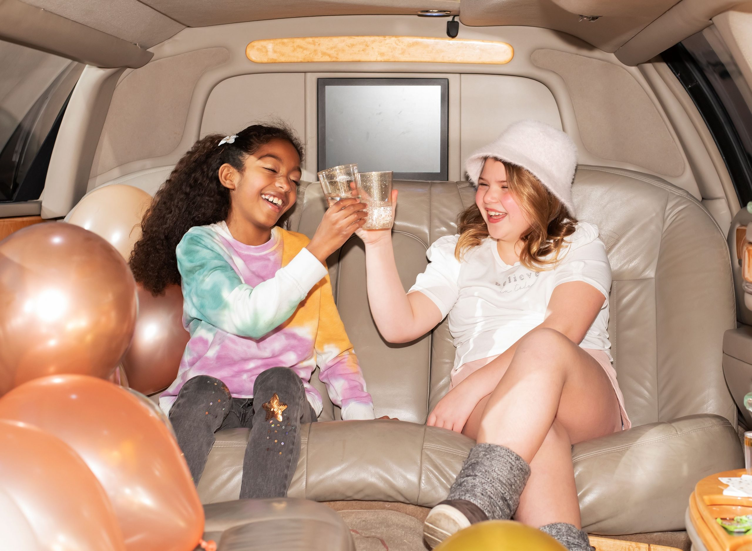 Girls sitting inside of limo before party